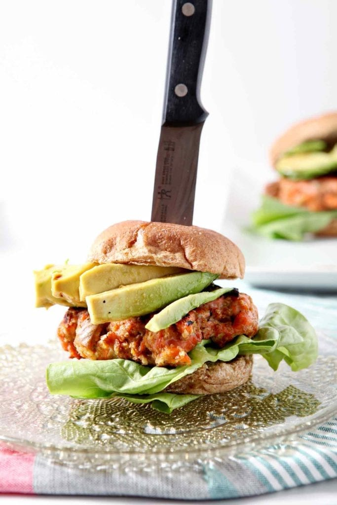 A salmon burger, speared with a knife and dressed to the nines, before serving.