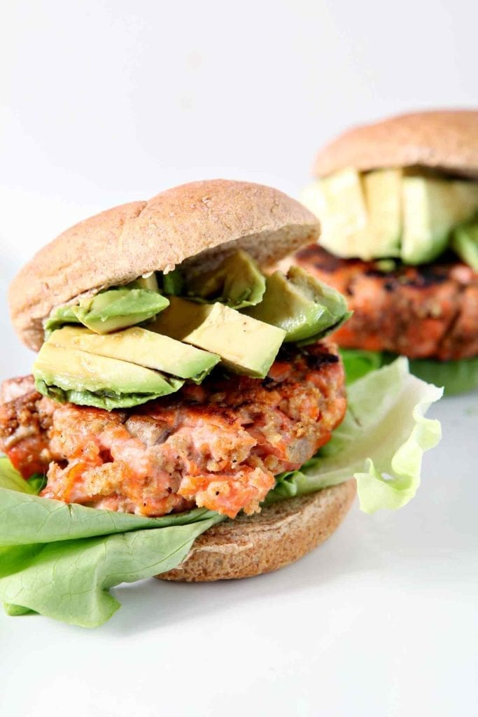 Two Classic Salmon Burgers are shown, dressed with lettuce and avocado, on whole wheat buns.