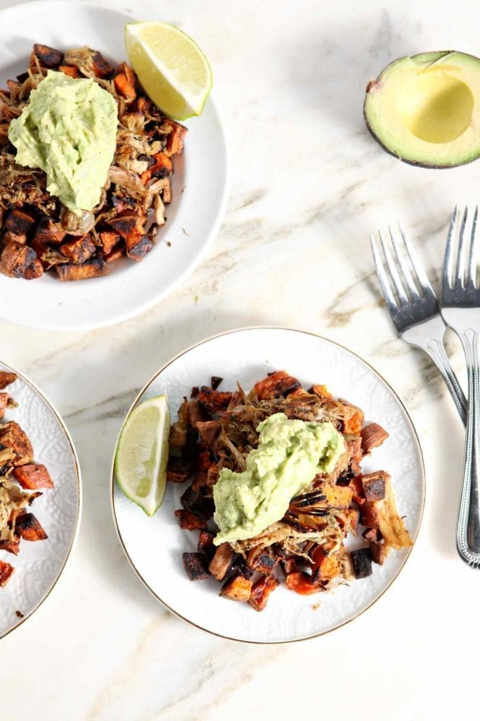 Three Whole30 Slow Cooker Pork Carnitas Plates sit on a marble background, layered and ready for eating