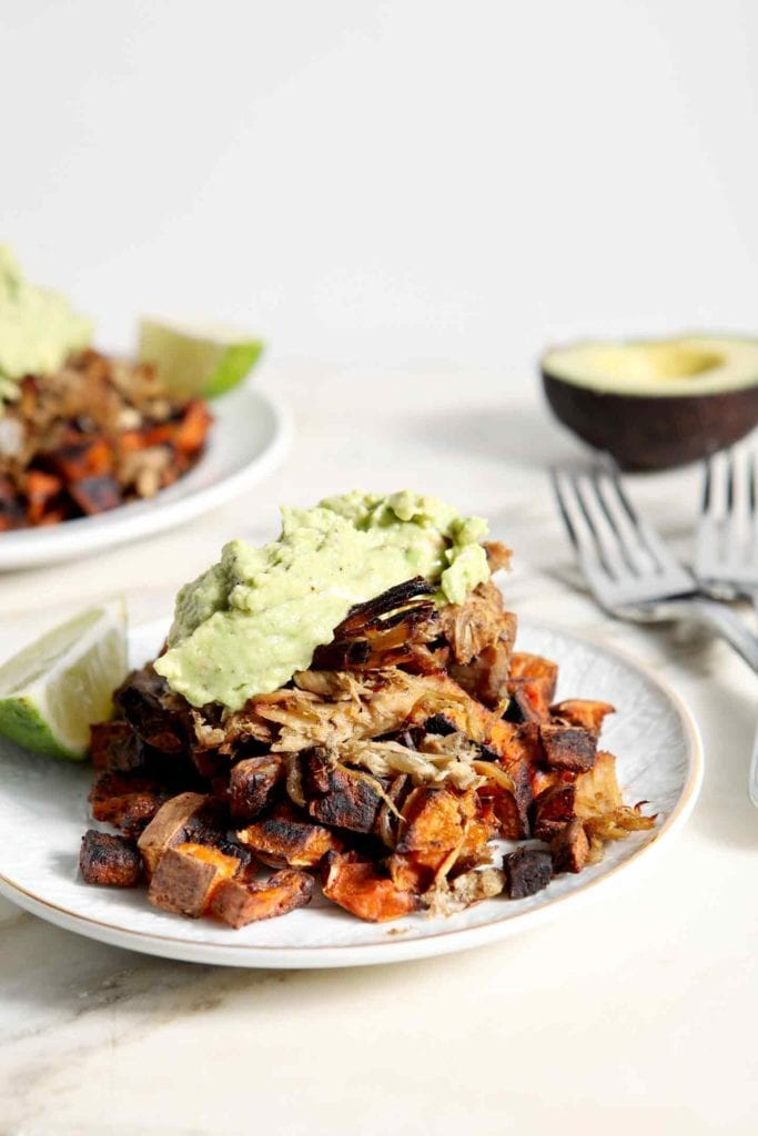Two plates of Whole30 Slow Cooker Pork Carnitas Plates, topped with fresh guacamole and garnished with a lime slice, sit on a marble tile.