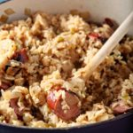 A Dutch oven of Jambalaya has a wooden spoon in it, close up