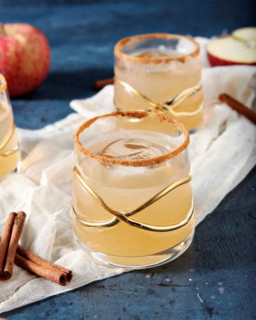 Close up of three Gin Apple Pie Drinks on a gauzy piece of fabric with apples and cinnamon sticks before being consumed