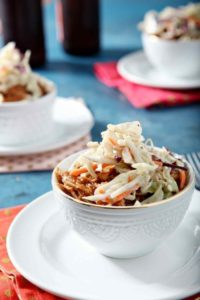 Two Pumpkin Pulled Pork Bowls sit on a blue background with colorful pink and orange napkins