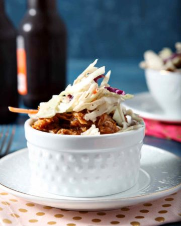 Two Pumpkin Pulled Pork Bowls are served in white bowls with beer on a blue backdrop