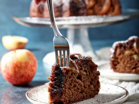 A fork cuts into a slice of Spiced Apple Upside Down Cake with Bourbon Caramel Glaze