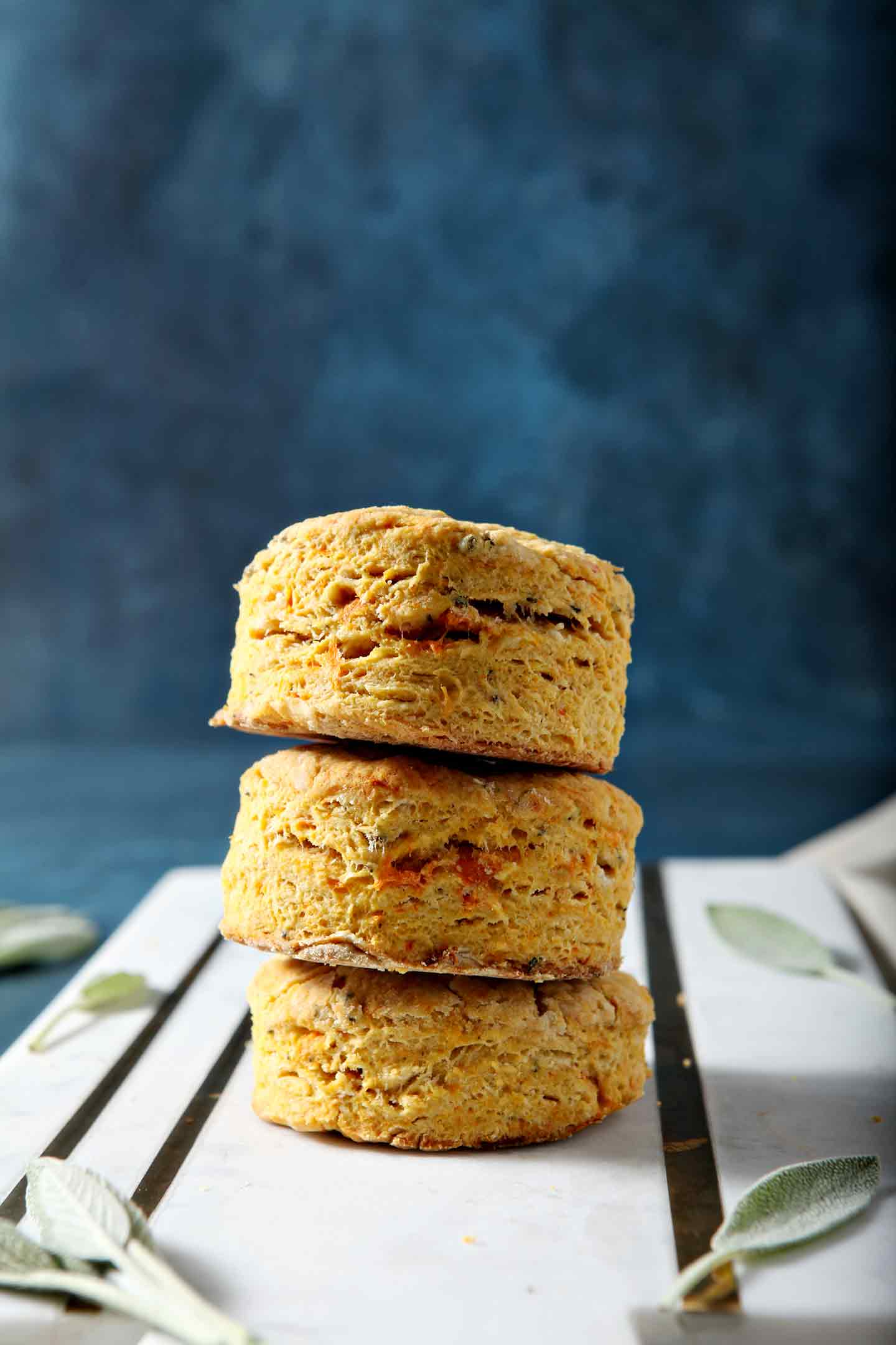 Bake Sage Sweet Potato Olive Oil Biscuits are stacked on top of one another on a marble serving platter