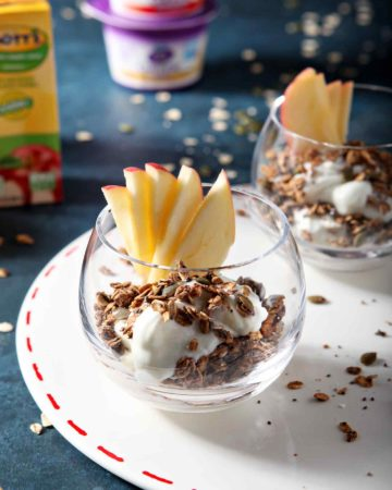 Two Apple Chai Spiced Yogurt Parfaits, displayed on a white platter, while sitting on a dark blue background with yogurt and apple juice containers in the background