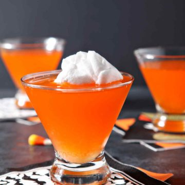Three bright orange Candy Corn Martinis sit on a black background