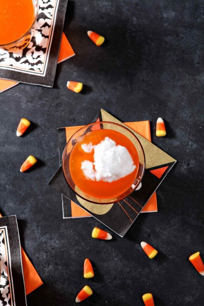 Overhead image of cotton candy floating on top of Candy Corn Martini liquors