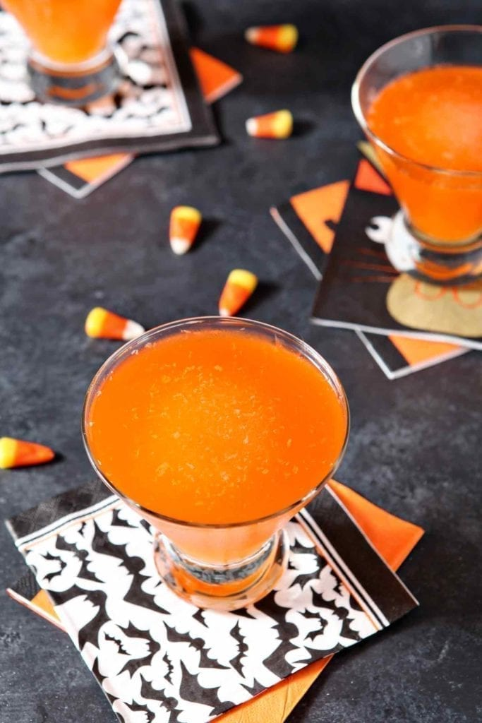 Three glasses of the Halloween drink, garnished with candy corn