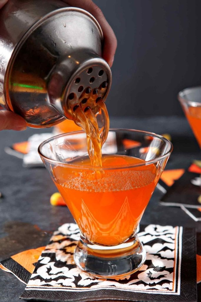 Candy corn vodka is poured into a martini glass