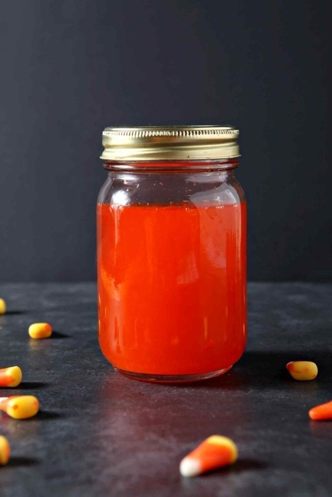 Candy corn vodka, in a mason jar, surrounded by candy corn