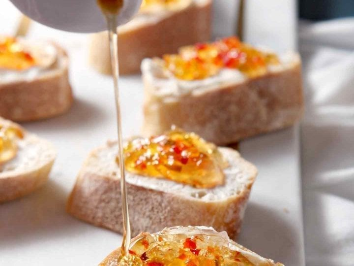 Honey is drizzled on top of Pepper Jelly Cream Cheese Bruschetta.