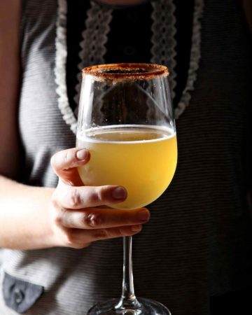 A woman holds a kombucha cocktail in a wine glass