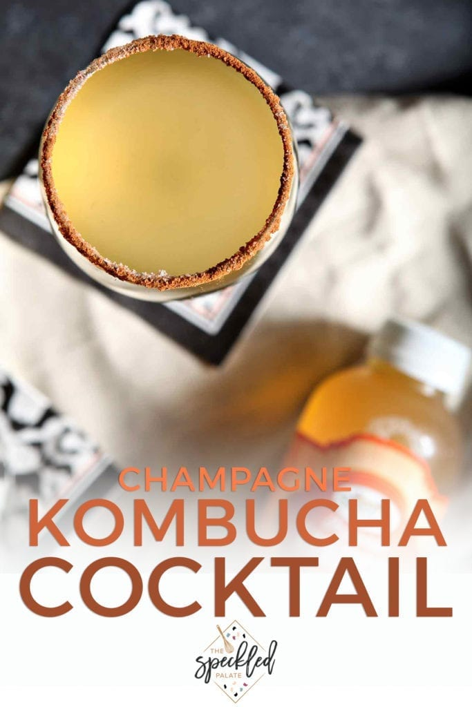 Overhead of a glass of golden liquid rimmed with and the text 'champagne kombucha cocktail'