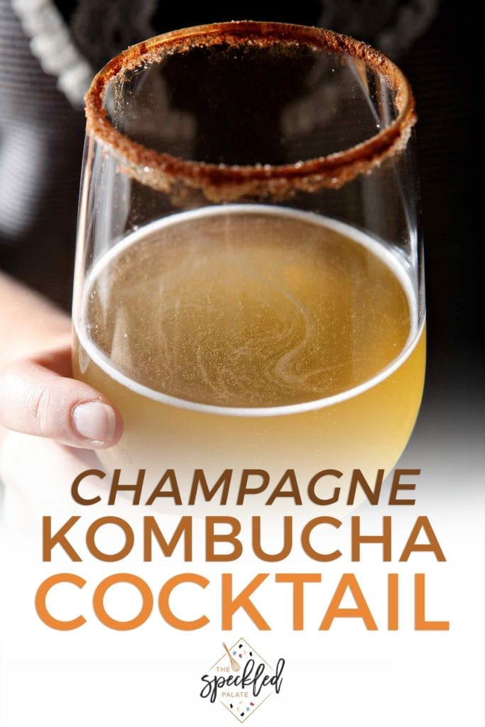 Close up of a woman holding a kombucha cocktail in a wine glass with the text 'champagne kombucha cocktail'