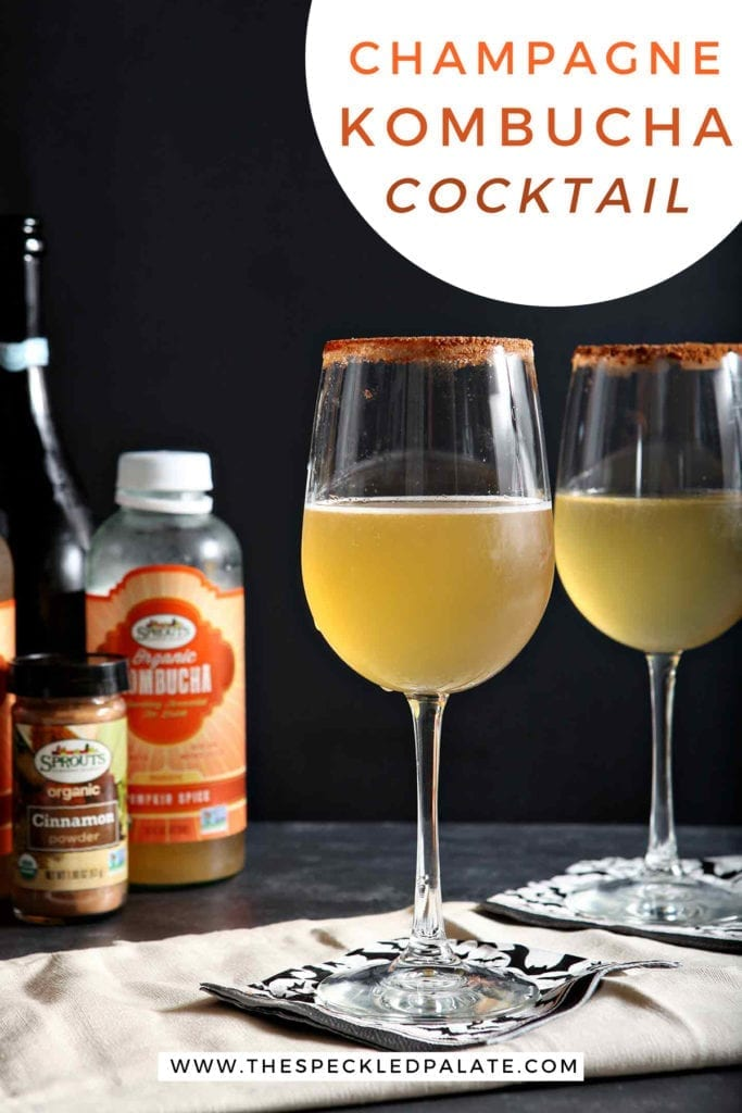 Two glasses holding pumpkin spice cocktails and the ingredients behind them on a black surface with the text 'champagne kombucha cocktail'