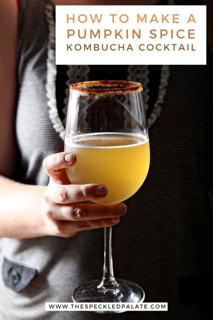 A woman holds a kombucha cocktail in a wine glass with the text 'how to make a pumpkin spice kombucha cocktail'