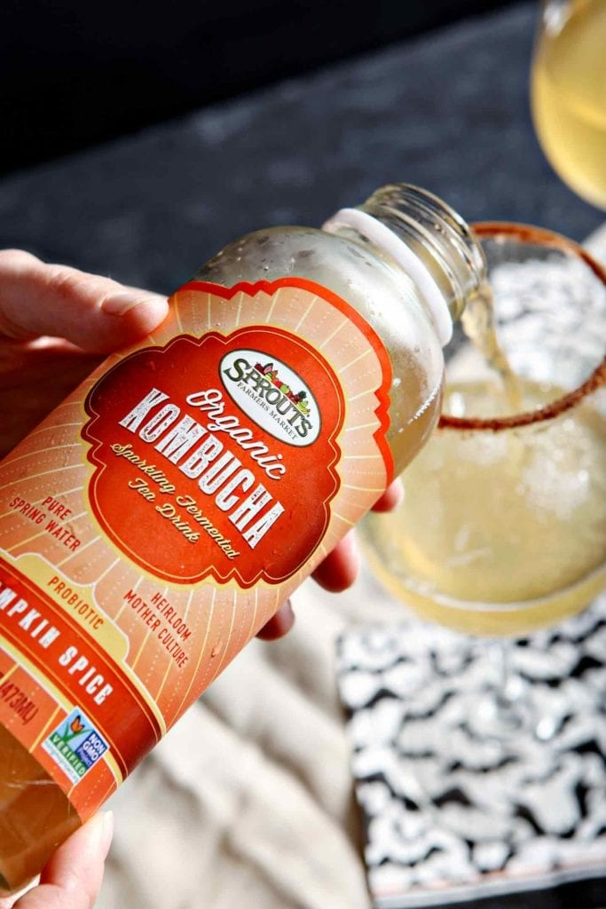 Sprouts branded kombucha pours into a wine glass