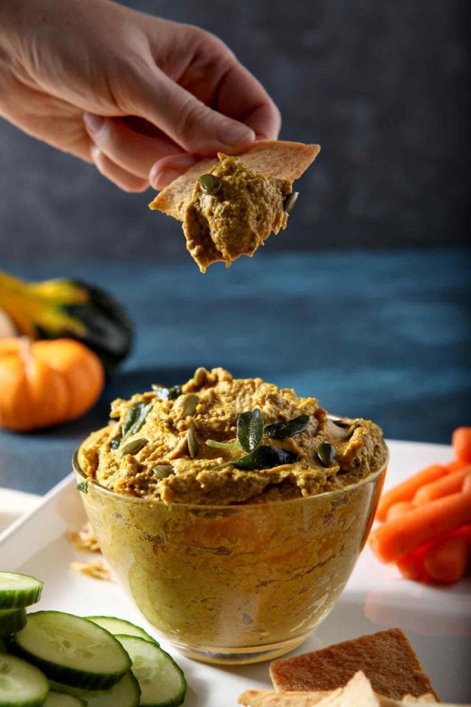 A person scoops a bite of Sage Pumpkin Hummus with a pita chip