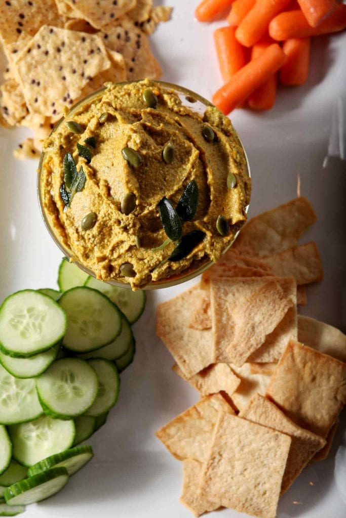 Overhead of the savory pumpkin dip, with cucumbers, carrots and chips