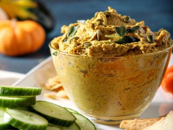 Close up of Sage Pumpkin Hummus, served with cucumber slices, carrots and pita chips