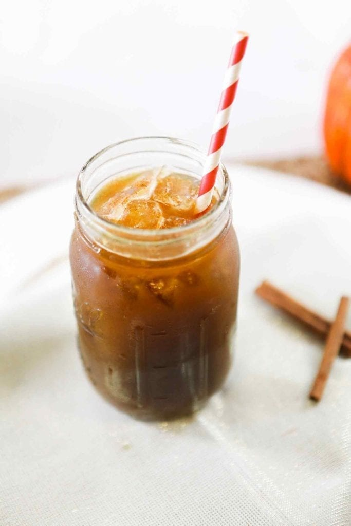 A coffee drink in a mason jar with a red and white striped straw on a white plate with cinnamon sticks around it