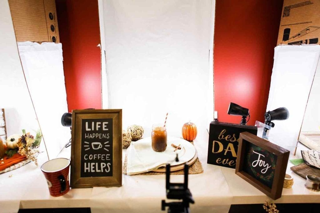A photo station at the Sprouts Blogger Retreat with lights, fall decor and signs