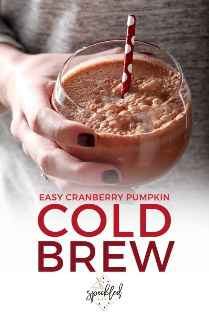 A woman holds a cold brew coffee drink in a glass with a red polka dot straw in her hand with the text 'easy cranberry pumpkin cold brew'