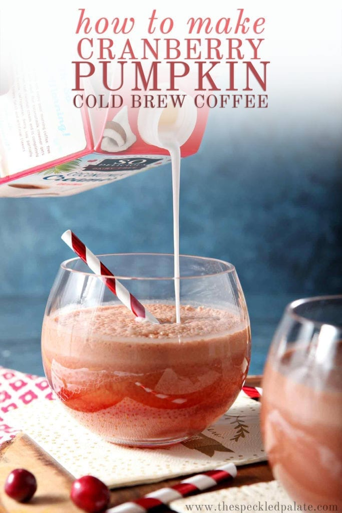 Pumpkin creamer is poured into a cold brew coffee drink in a glass on a wooden serving tray with the text 'how to make cranberry pumpkin cold brew coffee'