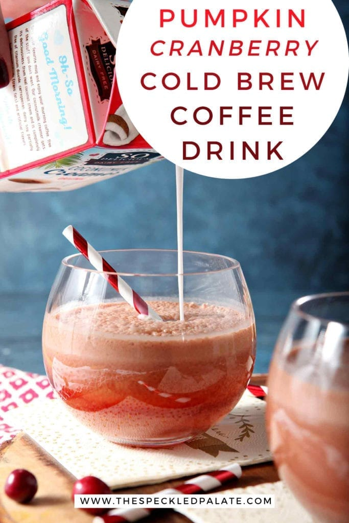 Pumpkin creamer is poured into a cold brew coffee drink in a glass on a wooden serving tray with the text 'pumpkin cranberry cold brew coffee drink'