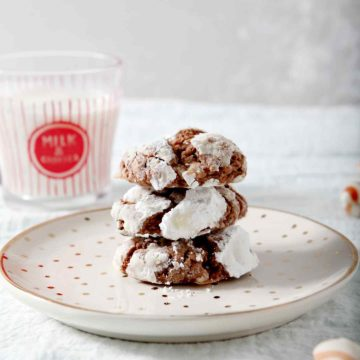 Peppermint Chocolate Crinkle Cookies are stacked on top of each other and served with milk