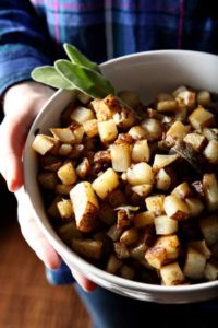 A woman holds a bowl of Sage Browned Butter Homemade Home Fries.