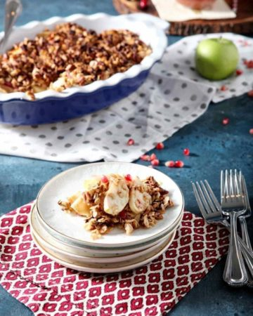A stack of plates holds a serving of Vegan Apple Crisp with Pomegranates on a dark blue background with the serving dish behind it