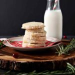 A stack of Ginger Rosemary Shortbread Cookies are served on a wooden platter with a glass of milk