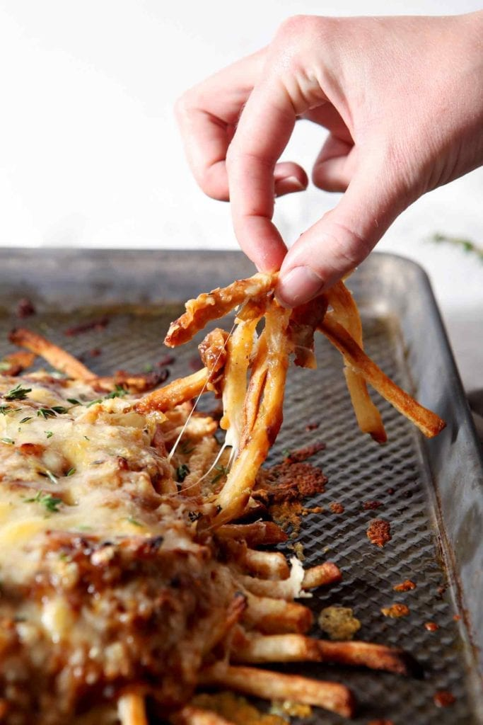 Fries from French Onion Poutine being pulled away from the baking sheet before eating