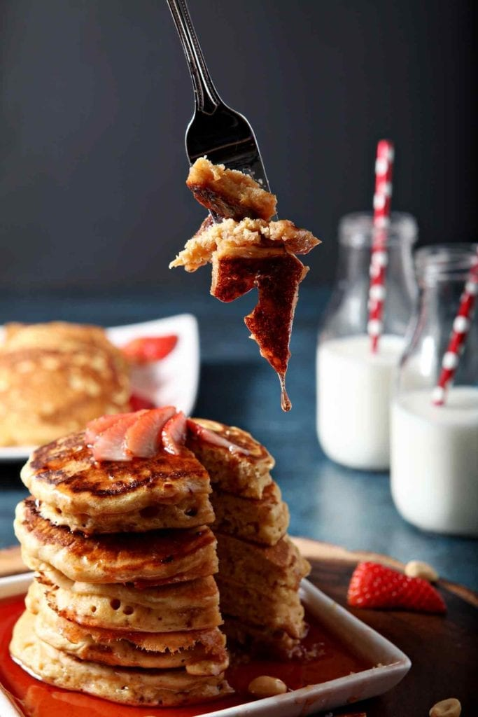 bite of pancakes on a fork, milk in the background