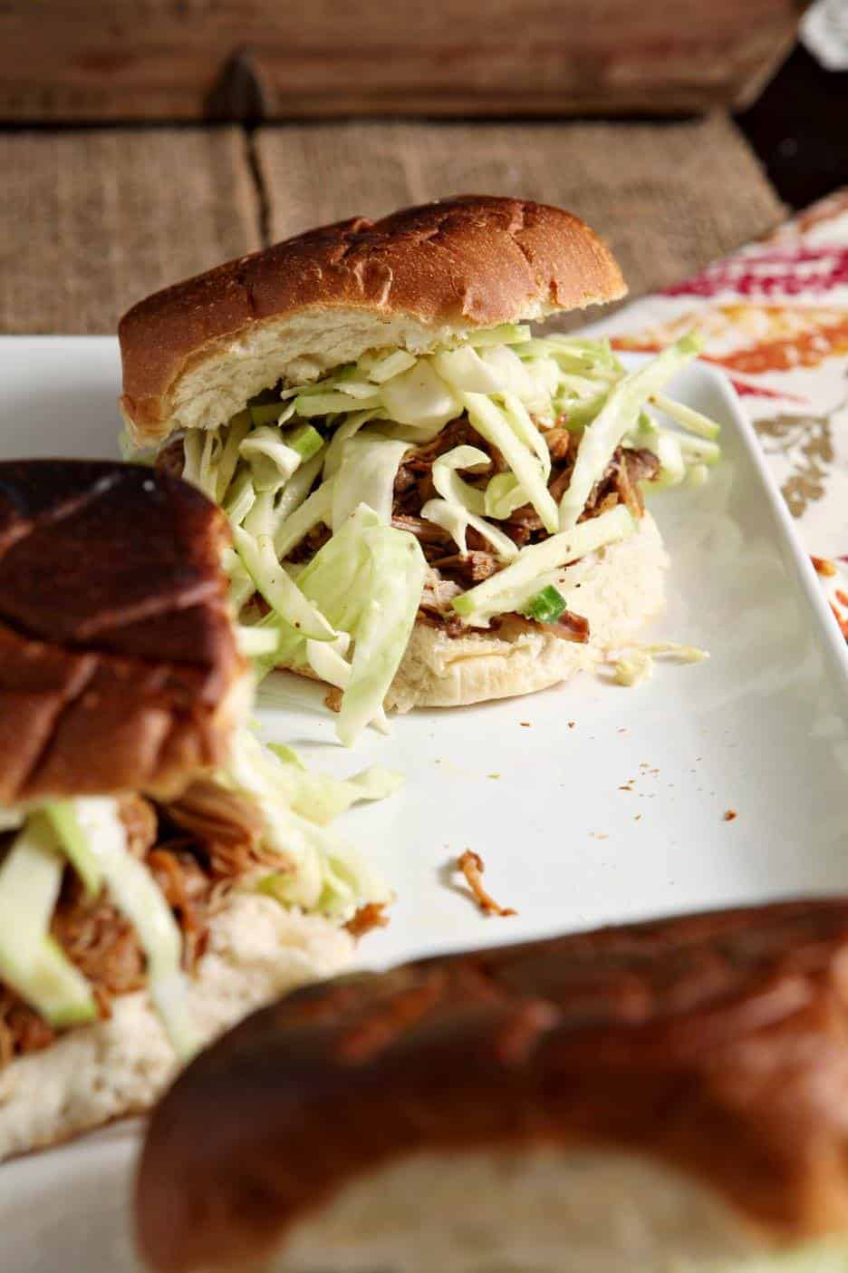Side shot of three Apple Cider Pork Sliders with Slaw on a table