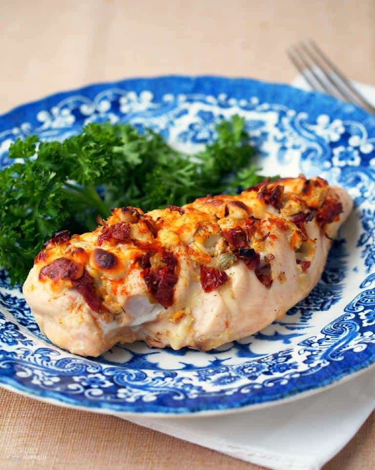 Hasselback Stuffed Chicken side shot on a blue plate with greens