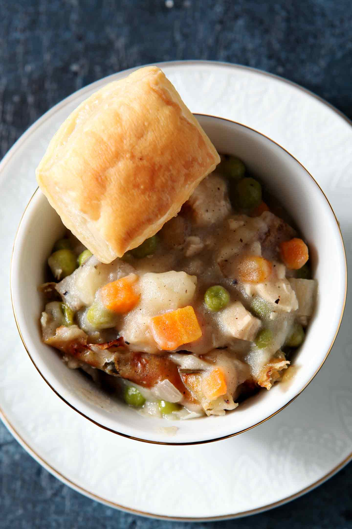 Overhead photo of an individual bowl of Homemade Chicken Pot Pie with a tiny piece of puff pastry on top, displayed on a blue background with the baking dish of pot pie in the background