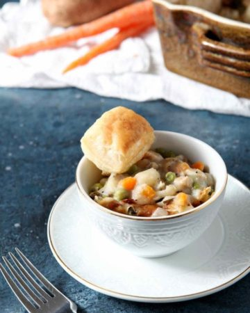 chicken pot pie in a white bowl with a biscuit