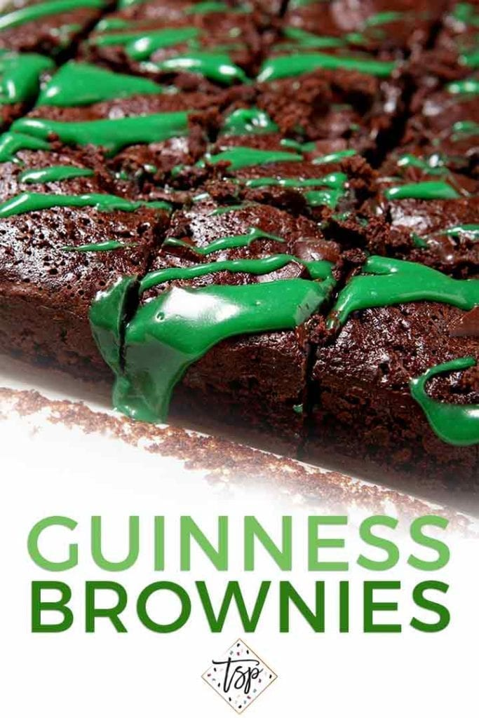 Close up of sliced brownies drizzled with green frosting in a pan with the text 'guinness brownies'