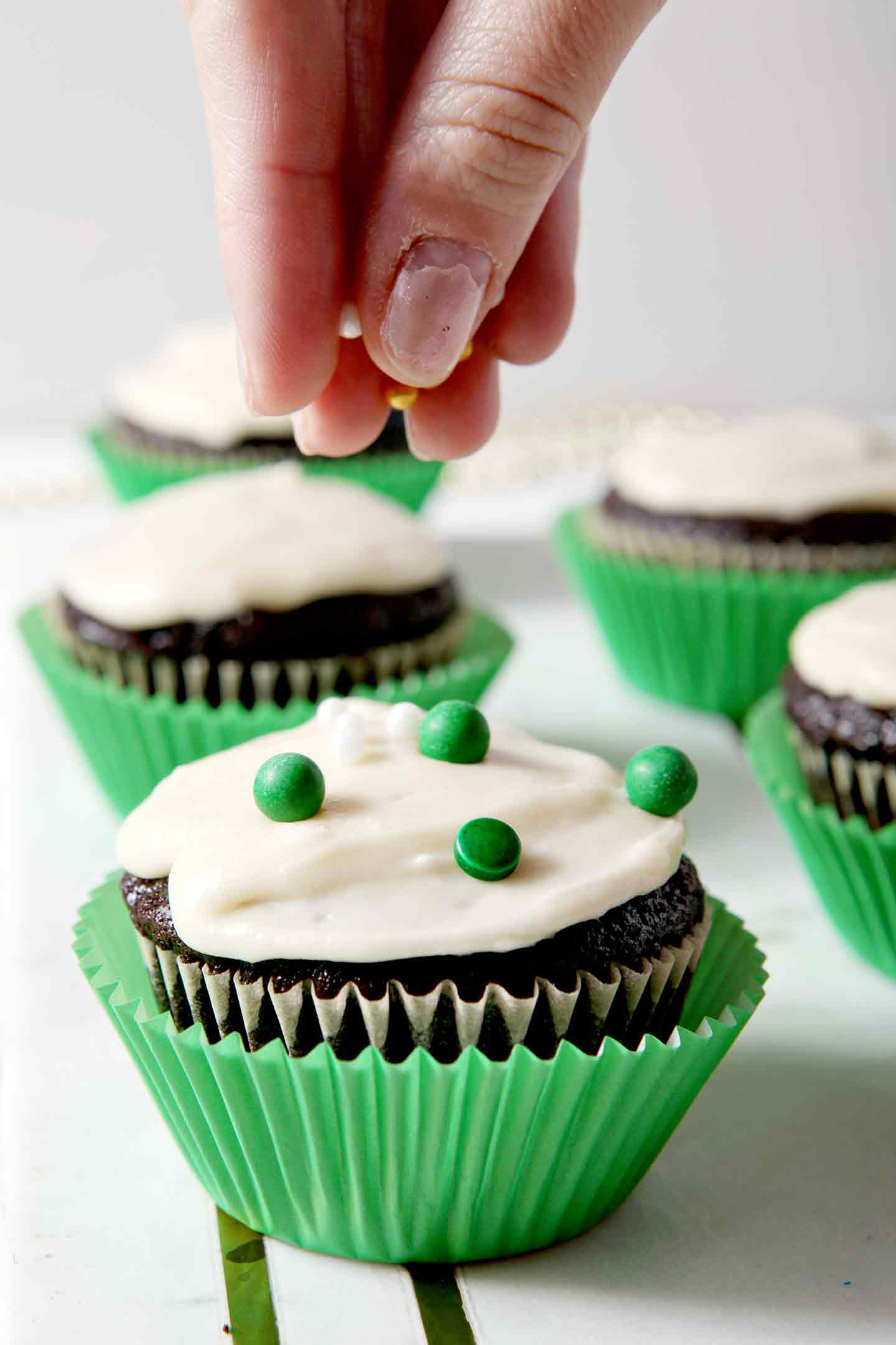 Chocolate Guinness Cupcakes, iced with Bailey's Icing, being decorated with green, white and gold sprinkles