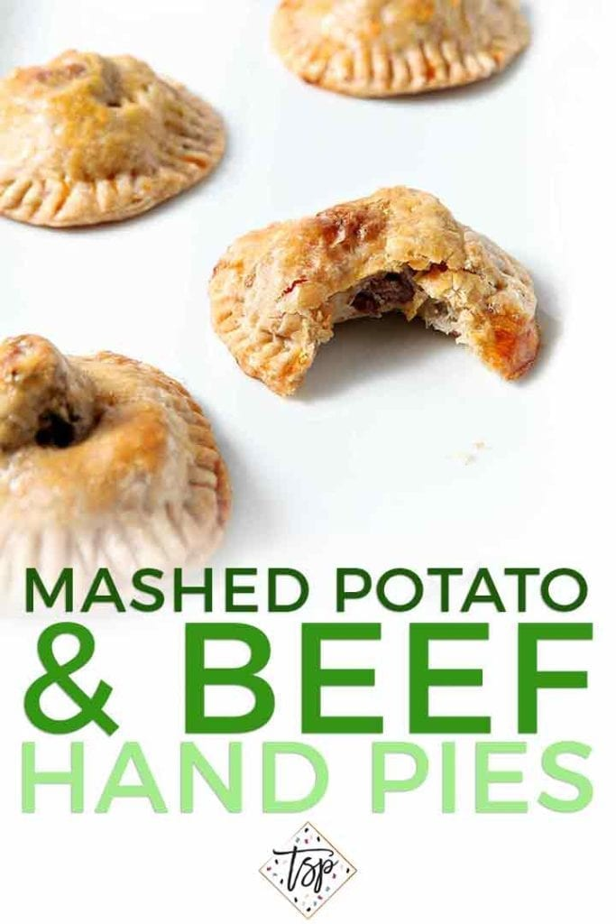 Closeup of a bitten-into Mashed Potato Beef Hand Pies with others on a white platter with the text 'Mashed Potato & Beef Hand Pies'