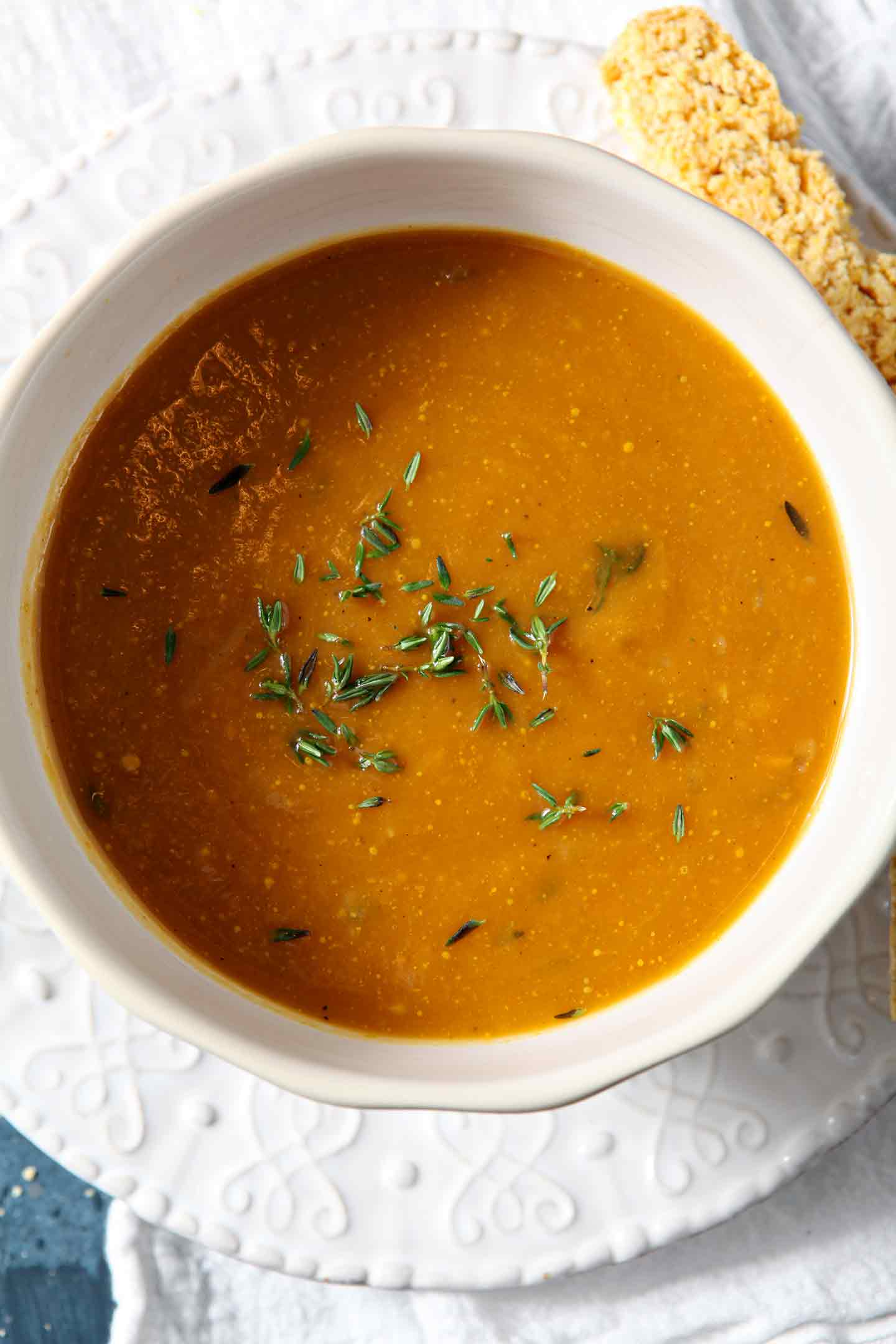 One bowl of Sweet Potato Bisque on a blue background with cornbread biscotti