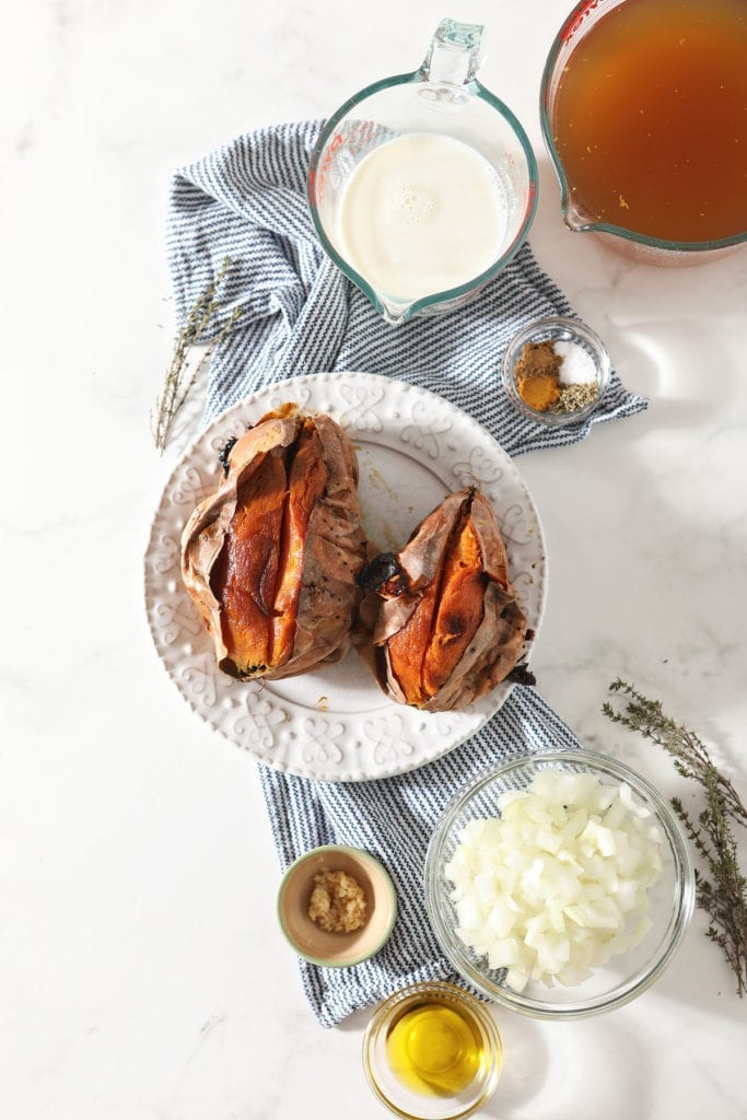 Roasted sweet potatoes and other ingredients sit on a blue striped towel on a marble countertop