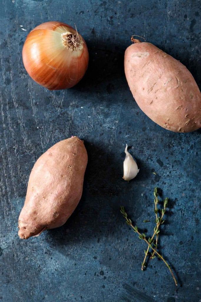 Two sweet potatoes, a clove of garlic, fresh thyme and an onion sit together on a dark countertop