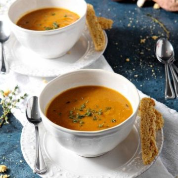 Two bowls of Sweet Potato Bisque on a blue background with cornbread biscotti