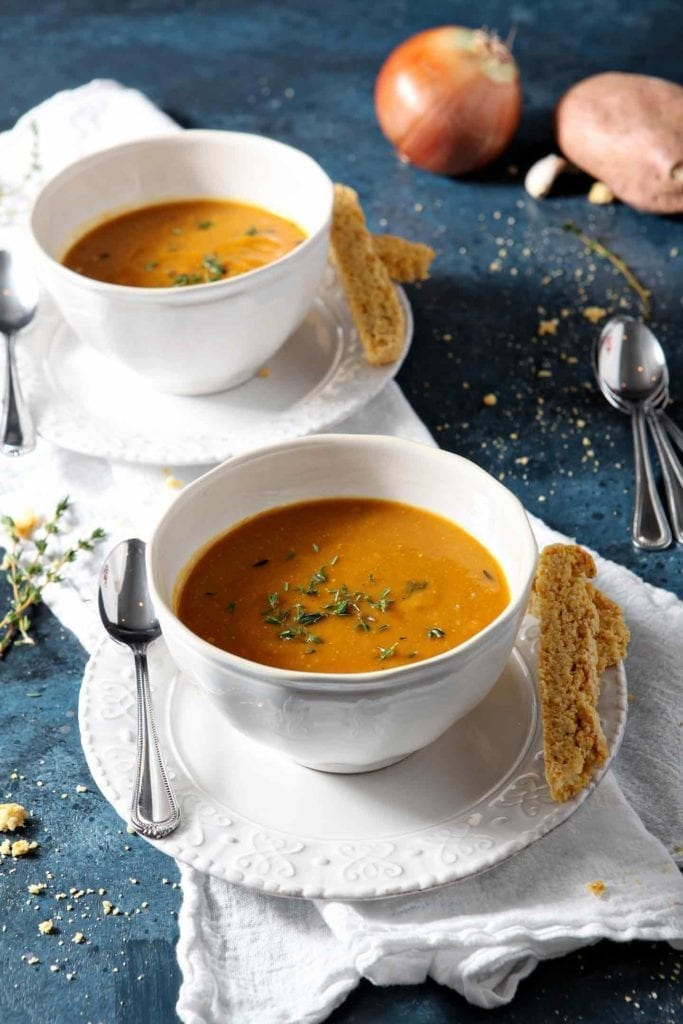 Two bowls of Sweet Potato Soup on a blue background with cornbread biscotti