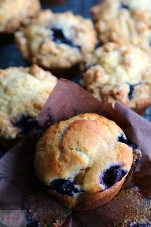 Easy Blueberry Peach Streusel Muffins from Pook's Pantry in dark baking cups, ready for consuming